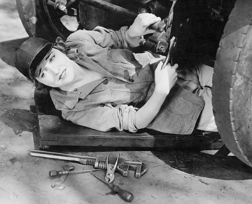 Female mechanic under car with tools